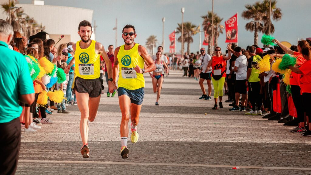7-best-ways-preparing-a-marathon-race-and-complete-two-marathon-friends-hold-each-other's-hand-just-before-finish-line