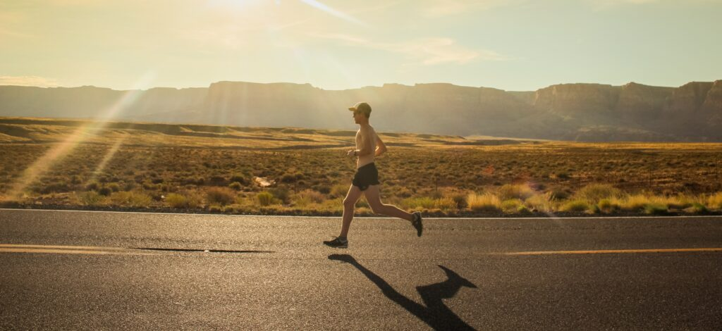 Marathon-training-for-beginners-man-running-on-road-in-open-landscape