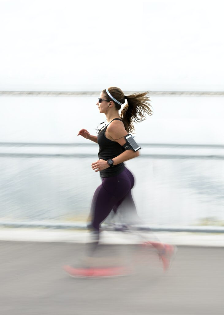 Best-Music-to-Running-strong-woman-running-with-earplugs