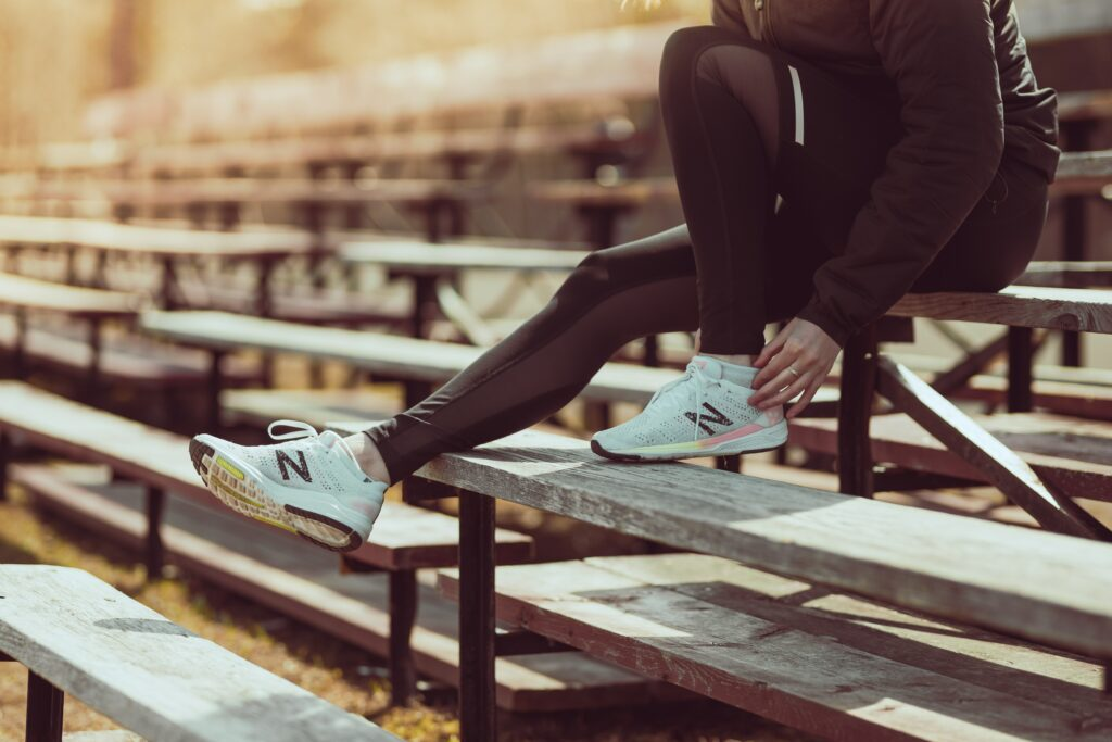 How-to-Train-For a-Marathon - 10-Tips-From-Top-Runners- Woman-sitting-and-check-her-running-shoe