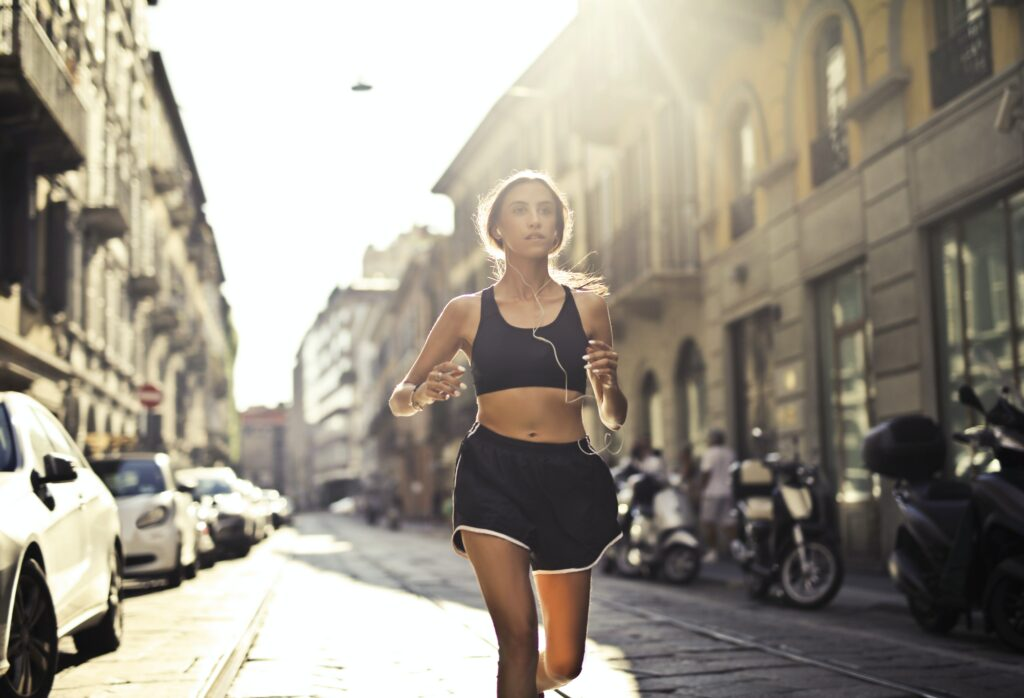 8-best-tips-for-music-to-running-training-Woman-with-earbuds-running-in-a-city